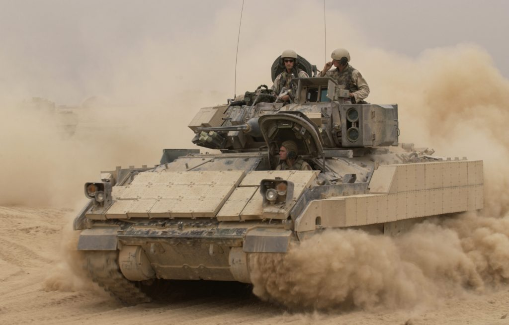 041030-F-2034C-040 An M2A2 Bradley Fighting Vehicle kicks up plumes of dust as it leaves Forward Operating Base MacKenzie in Iraq for a mission on Oct. 30, 2004. The Bradley is assigned to Alpha Troop, 1st Battalion, 4th Cavalry Regiment, 1st Infantry Division. DoD photo by Staff Sgt. Shane A. Cuomo, U.S. Air Force. (Released)