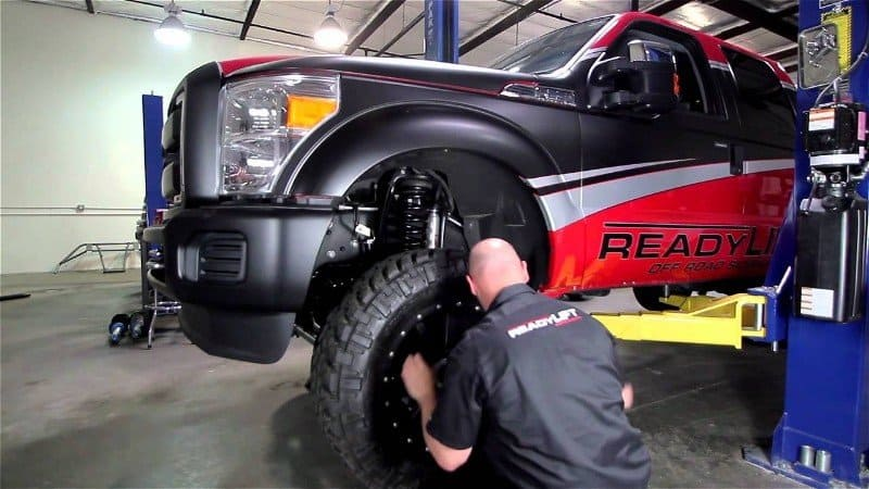 mechanic installing lift kit